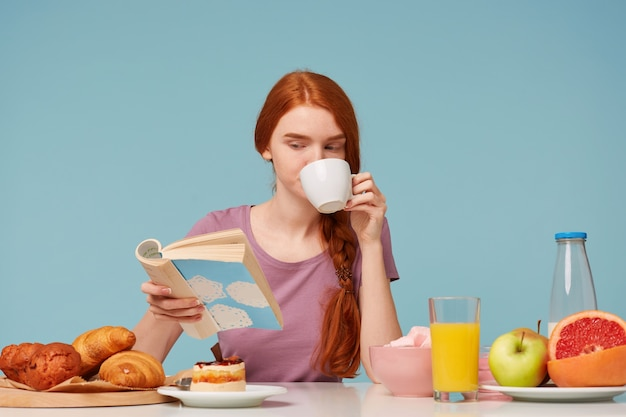Cleaver red-haired woman with braided hair, sitting at a table, drinks from white cup delicious tea, has breakfast reading book