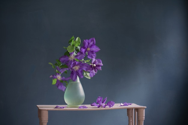 Clematis flowers in glass vase  on vintage wooden shelf