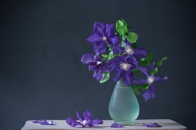 Цветы клематиса в стеклянной вазе на старинной деревянной полке