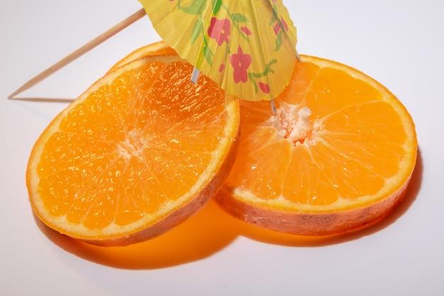 Кусочки фруктов клементинов, изолированные на белом фоне с коктейльным зонтиком.