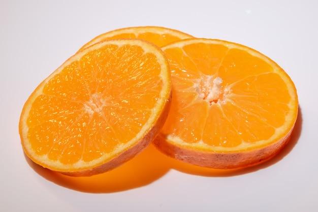 Кусочки фруктов клементинов изолированные на крупном плане белой поверхности.