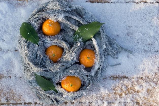 雪を背景にクリスマスの装飾として葉とクレメンタインみかん。