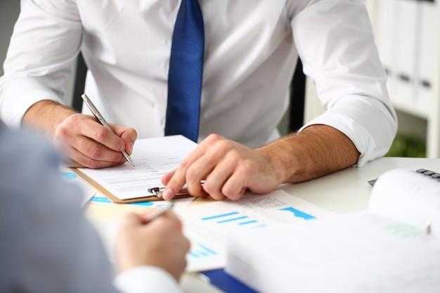 Клерк человек на рабочем месте в офисе с серебряной ручкой в руках