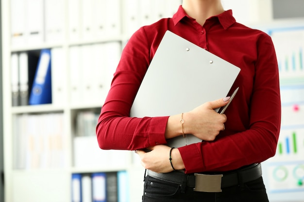 Clerk in red blouse hugging grey document pad closeup