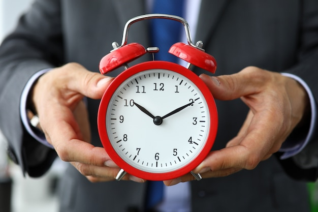 Clerk in suit and tie hold red vintage clock