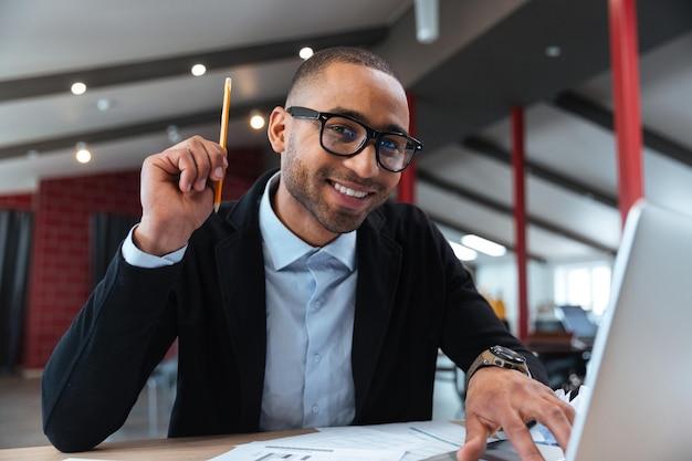 Умный бизнесмен, имеющий хорошую идею, держа карандаш