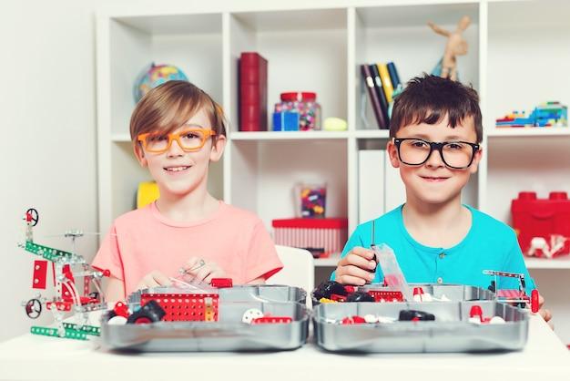 テーブルでdiy構造を作成する賢い子供たち。金属コンストラクターで遊んでいる幸せな男の子。教育、工学、趣味の概念。創造的な機械ロボットをやっている面白いクラスメート。