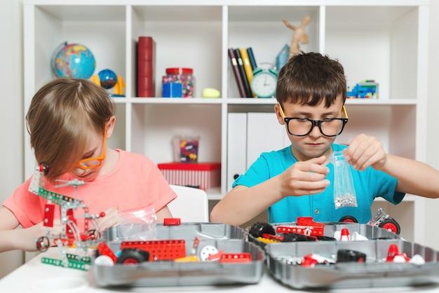 テーブルでdiy構造を作成する賢い子供たち。金属コンストラクターで遊んでいる幸せな男の子。教育、工学、趣味の概念