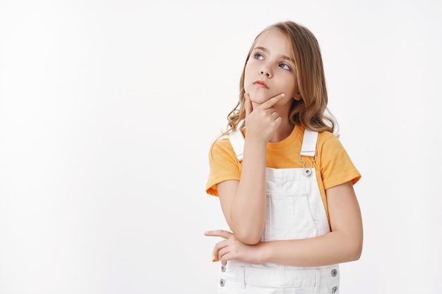 Умная креативная симпатичная молодая белокурая маленькая девочка задумчиво смотрит вверх, касается подбородка, делая выбор, серьезный взгляд сверху копирует пространство, обдумывает выбор, решает головоломку, стоит на белой стене, сосредоточенная, думая
