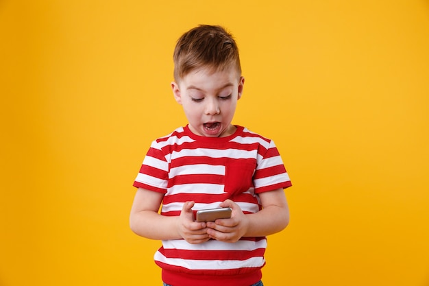 Clever excited little boy reading message on mobile phone