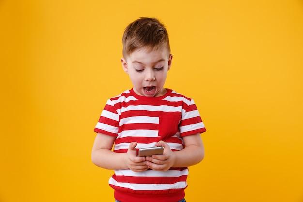 Умный взволнованный маленький мальчик читает сообщение на мобильном телефоне