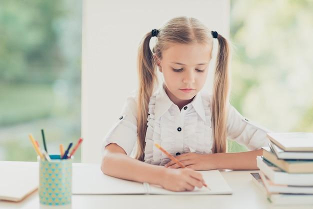 家の机で宿題をする賢い女の子