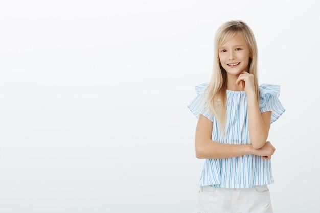 賢い女の子は答えを知っており、興味深いコンセプトを提案したいと考えています。スマートファッショナブルな子供のブラウスでブロンドの髪、あごの下で手を握って自信を持って笑顔、灰色の壁の上に立ってのショット