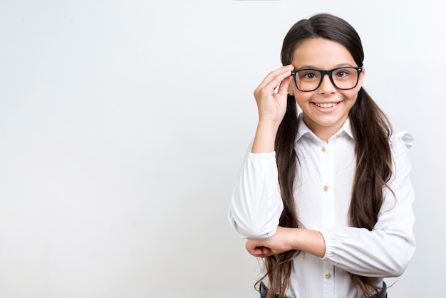 Clever hispanic schoolgirl standing in glasses