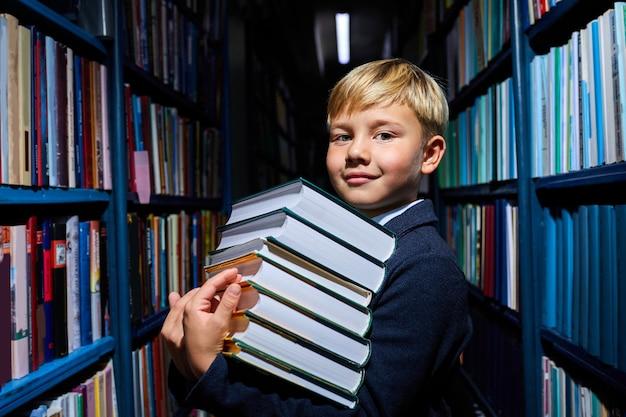 学校、図書館、学校の服装で準備する手に本の山を持つ賢い子供の男の子