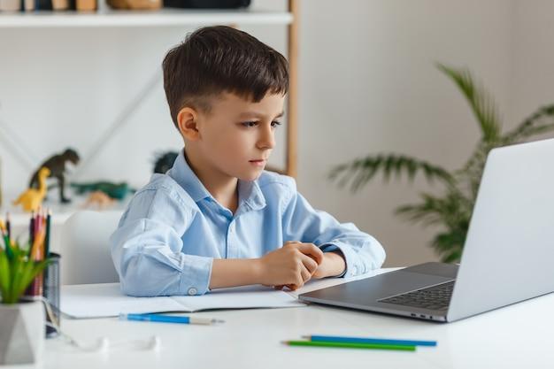 ノートパソコンとインターネットを使用して宿題をしている賢い子供