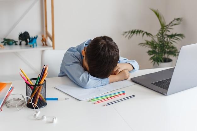 노트북과 인터넷을 사용하여 어려운 숙제를 배우는 데 지친 영리한 아이. 화상 통화를 통한 초등학교 e- 러닝. 집에서 온라인으로 공부하는 소년
