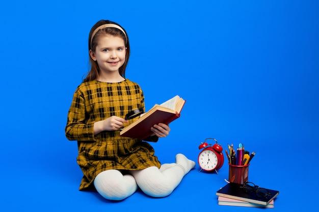 Умный маленький ребенок с помощью лупы, чтобы читать книгу во время учебы