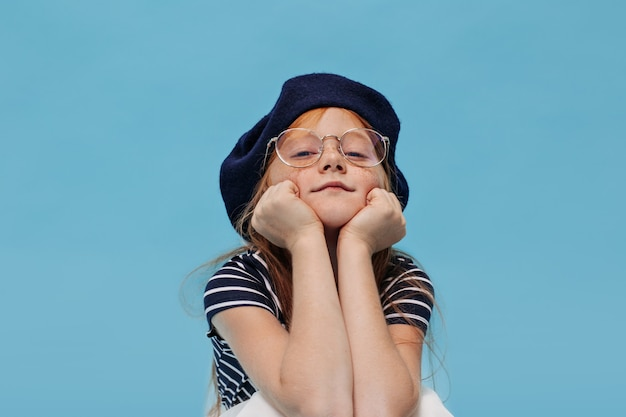 Clever little girl with freckles in stylish hat and clear glasses posing and looking at front on blue isolated wall