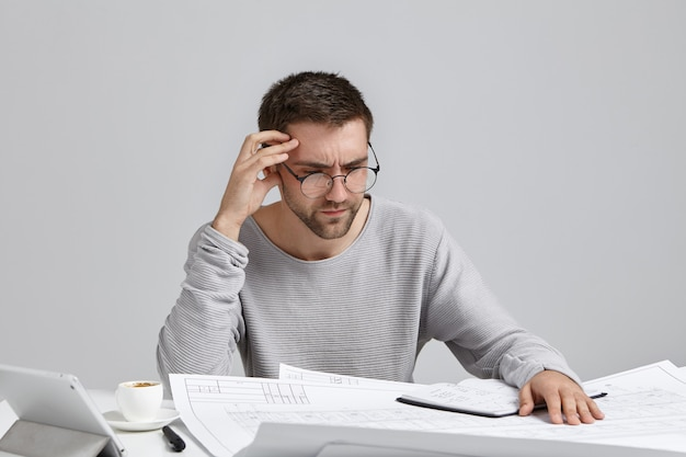 Clever male creative worker tries to concentrate on drawings, doesn`t understand where is his mistake