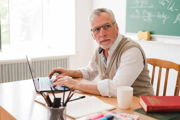 Clever old professor using laptop in classroom