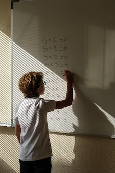 Clever pupil solving mathematical example during lesson at school