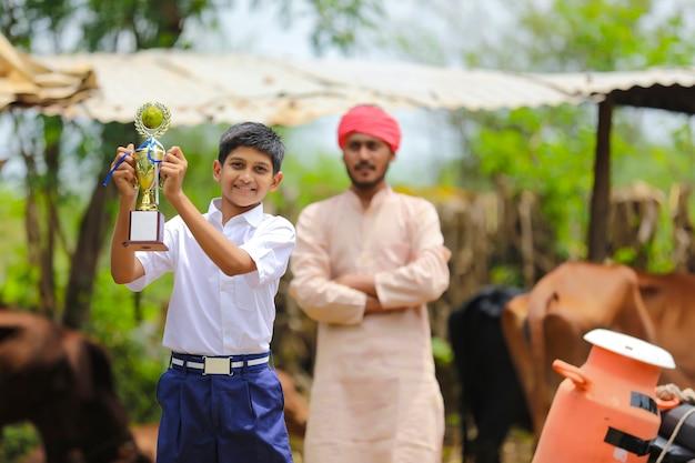 Умный школьник держит победный трофей и стоит со своим отцом