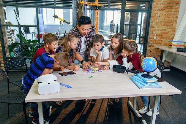 アジアの男性教師がいる賢い学校の子供たちは、扇風機と電球を使って電子コンストラクターを調査しています。科学者が学校で技術プロジェクトに取り組んでいる創造的な生徒。