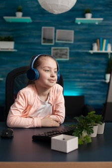 Clever school girl using computer monitor at home