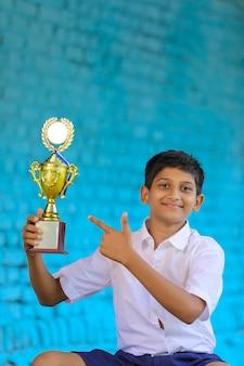 Умный школьник ставит свой трофей победителем школьных олимпиад.