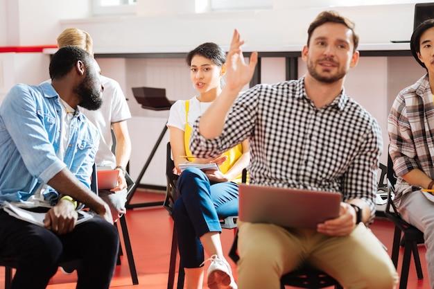영리한 학생. 밝은 방에 앉아 수업에서 토론에 참여하는 동안 관심을 보이는 활동적인 영리한 학생들