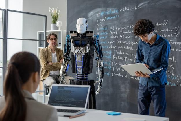 クラスの前で黒板のそばに立って、ロボットの能力と特徴のプレゼンテーションを行うラップトップを持つ賢い10代の男