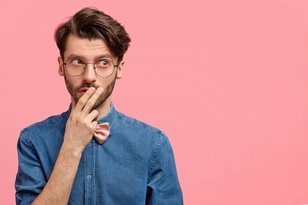 Intelligente e premuroso maschio con la barba lunga guarda pensieroso in lontananza, tocca la bocca con la mano, è immerso nei pensieri, pensa a qualcosa di importante, vestito con una giacca di jeans, isolato su un muro rosa