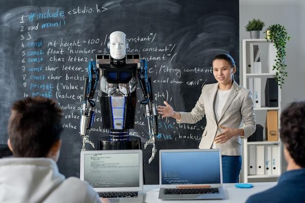 Умная молодая студентка показывает одноклассникам новую модель робота-автоматика, стоя у доски