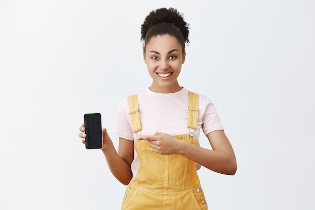 このボタンをクリックします。黄色のトレンディなダンガリーでのんきなフレンドリーなアフリカの女子学生、スマートフォンを持って人差し指でデバイスを指さし、広く笑って、素晴らしいアプリを提案します