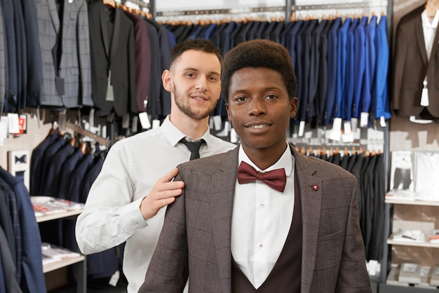 Client and assistant posing in stylish clothing in boutique.
