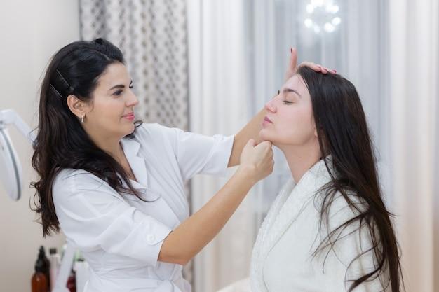 Un cliente all'appuntamento di un'estetista, consulenza, modellamento del viso, preparazione per le procedure imminenti, esame visivo delle aree problematiche