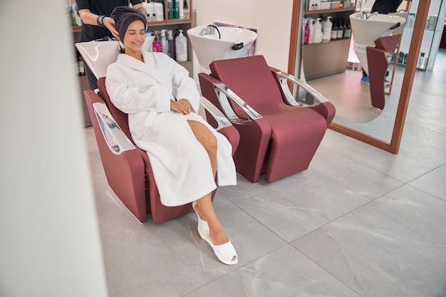 Client in the comfortable robe and slippers having good time