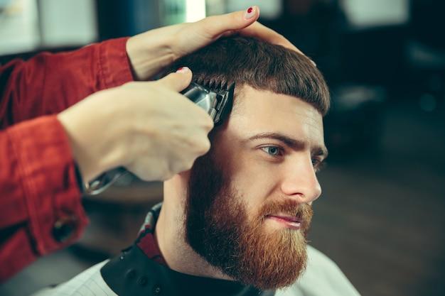 Cliente durante la rasatura della barba nel negozio di barbiere. barbiere femminile al salone. parità dei sessi. donna nella professione maschile. le mani si chiudono
