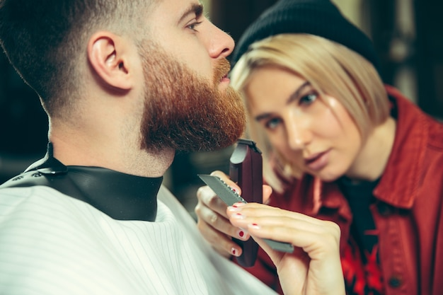 Client during beard shaving in barbershop. female barber at salon. gender equality. woman in the male profession.