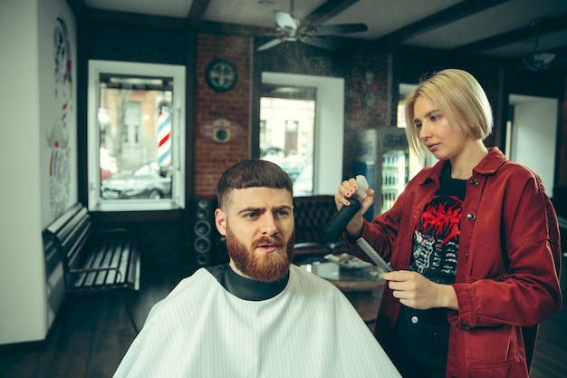Cliente durante la rasatura della barba nel negozio di barbiere. barbiere femminile al salone. parità dei sessi. donna nella professione maschile.