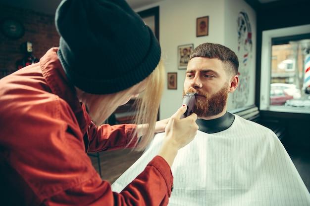 Cliente durante la rasatura della barba nel negozio di barbiere. barbiere femminile al salone. parità dei sessi