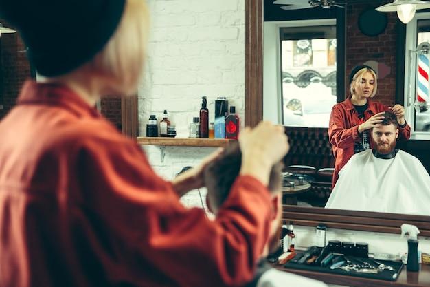Client during beard shaving in barbershop. female barber at salon. gender equality