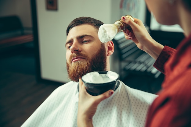 Client during beard shaving in barbershop.