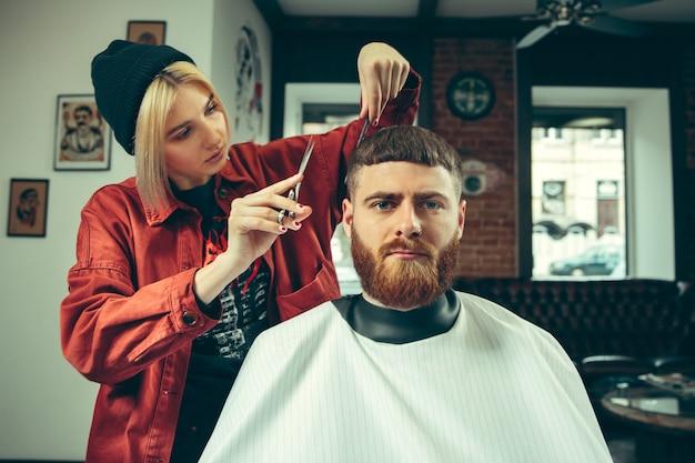 Cliente durante la rasatura della barba nel negozio di barbiere.