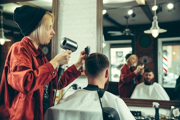 Client during beard shaving in barbershop.