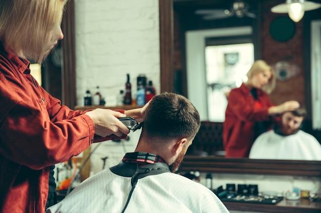 Cliente durante la rasatura della barba nel negozio di barbiere