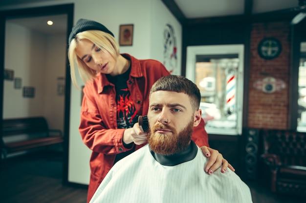 Client during beard shaving in barbershop