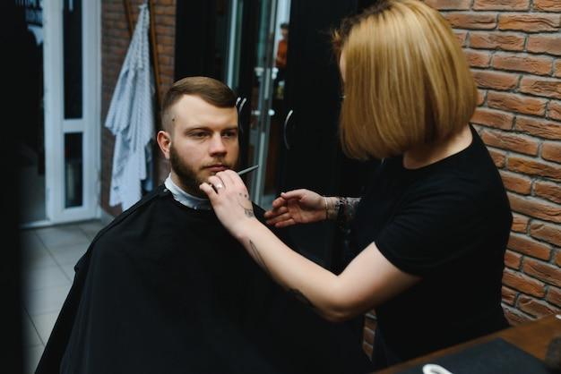 Клиент во время бритья бороды в парикмахерской