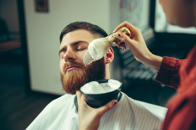 이발소에서 수염을 면도하는 동안 클라이언트. 살롱에서 여성 이발사. 남녀 평등. 남성 직업에있는 여자.